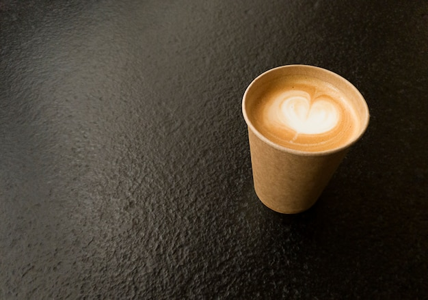 Xícara de café artesanal com formato de coração. copie o espaço em uma mesa texturizada preta.