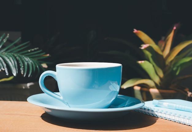 Xícara de café azul com caderno e caneta na mesa de madeira no jardim