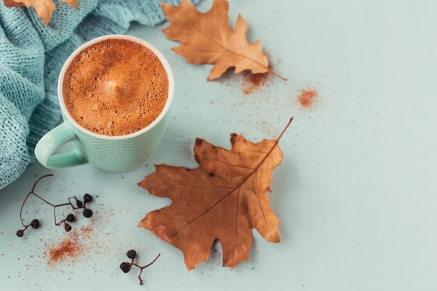 Xícara de café azul com folhas secas outonais e frutas secas em fundo azul claro