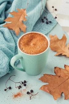 Xícara de café azul com folhas secas outonais e frutos secos em azul claro