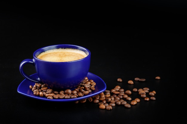Xícara de café azul e grãos de café em uma bandeja em um fundo preto