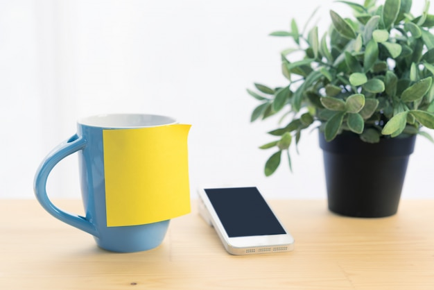 Xícara de café azul e post-it note no topo da mesa de madeira