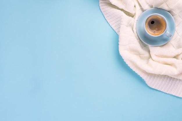 Xícara de café azul na manta sobre o fundo do papel azul com copyspace, configuração lisa. inverno acolhedor