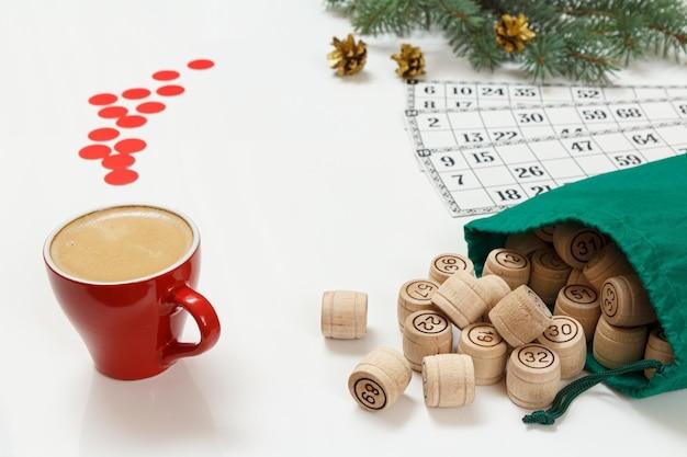 Xícara de café, barris de loto de madeira com um saco verde e cartas de jogo