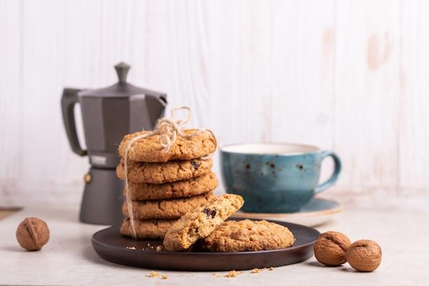 Xícara de café, biscoitos de aveia, cafeteira em fundo branco de madeira.