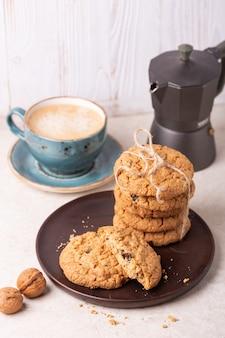 Xícara de café, biscoitos de aveia, cafeteira
