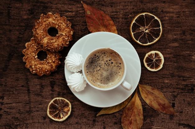 Xícara de café, biscoitos e folhas de outono em uma mesa de madeira, vista superior,