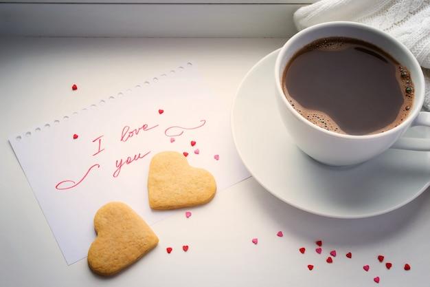 Xícara de café, biscoitos em forma de coração e uma declaração de amor.