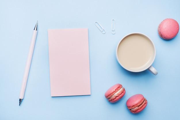 Xícara de café, biscoitos macaroon e bloco de notas com lay plana