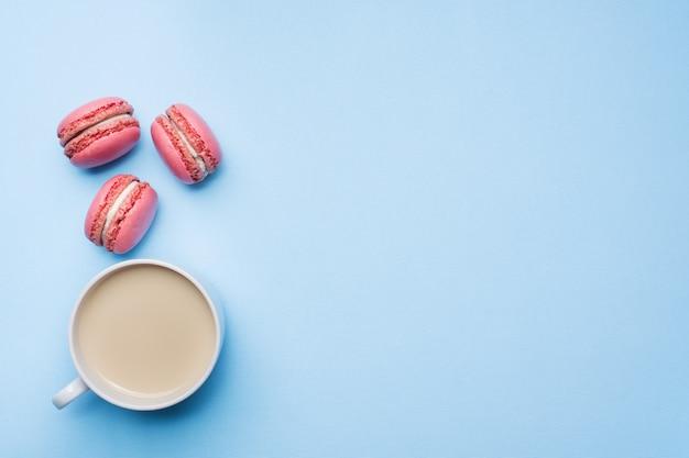 Xícara de café biscoitos macaroon em fundo azul pastel com lay plana