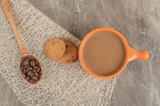 Xícara de café, biscoitos na superfície de mármore com grãos de café