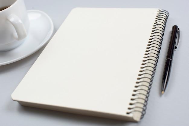 Xícara de café; bloco de notas em espiral fechado e caneta em fundo cinza