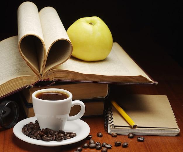 Xícara de café, bloco de notas, maçã e livro aberto