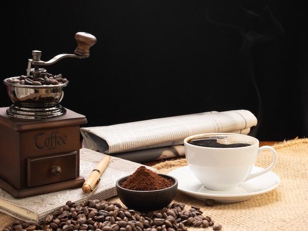 Xícara de café branca a vapor com moedor, grãos torrados, pó de café, jornal e caderno sobre hessian de serapilheira no fundo da mesa de madeira de grunge