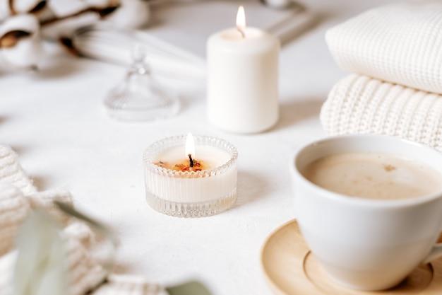 Xícara de café branca, algodão, velas.
