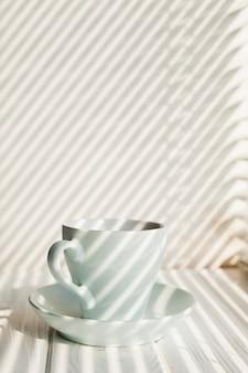 Xícara de café branca cerâmica com pires perto na mesa de madeira