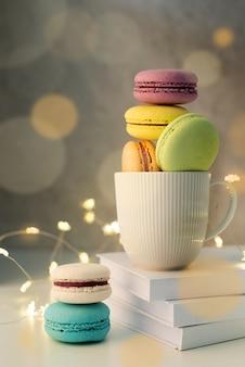 Xícara de café branca cheia de biscoitos na mesa, luzes de fada e fundo de bokeh