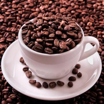 Xícara de café branca cheia de feijão assado close-up