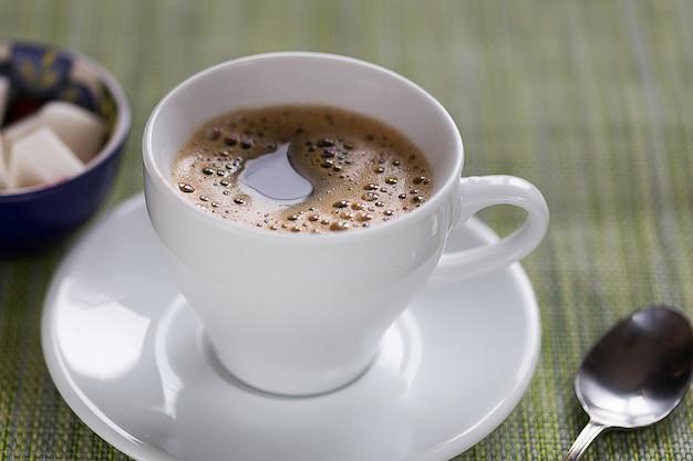 Xícara de café branca, colher de chá e açúcar sobre uma mesa