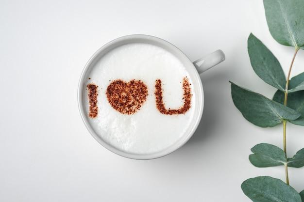 Xícara de café branca com a inscrição na espuma - eu te amo e ramo com folhas de eucalipto
