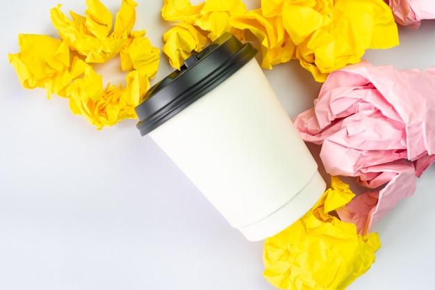 Xícara de café branca com bolas de papel desintegrado colorido sobre fundo branco