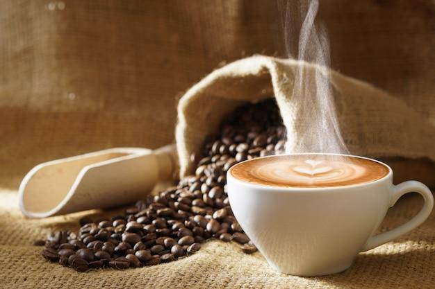 Xícara de café branca com fumaça de vapor quente e grãos de café torrados em torno de