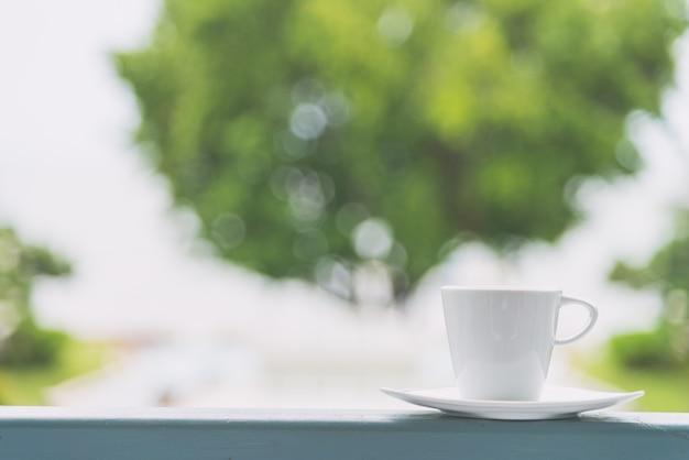 Xícara de café branca com fundo de vista ao ar livre - efeito de filtro vintage