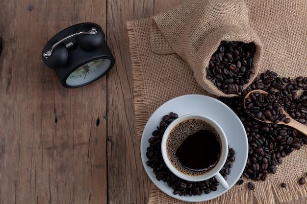 Xícara de café branca com grãos de café e despertador em fundo de madeira
