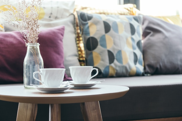 Xícara de café branca com vaso de flores na decoração de mesa com travesseiro no sofá