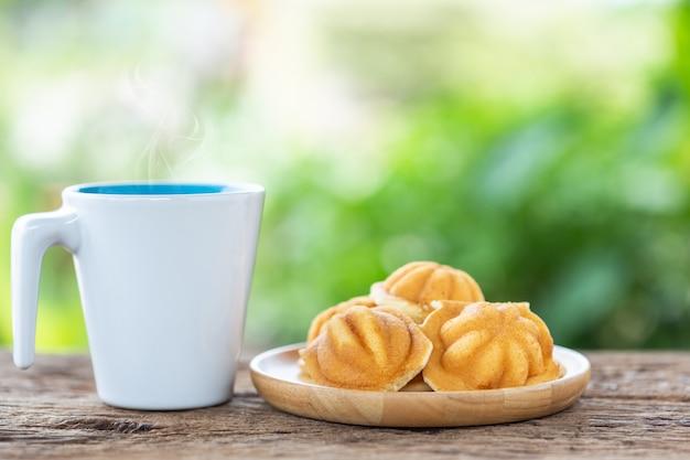 Xícara de café branca e bolos de ovo antigo na mesa de madeira com borrão luz bokeh de fundo