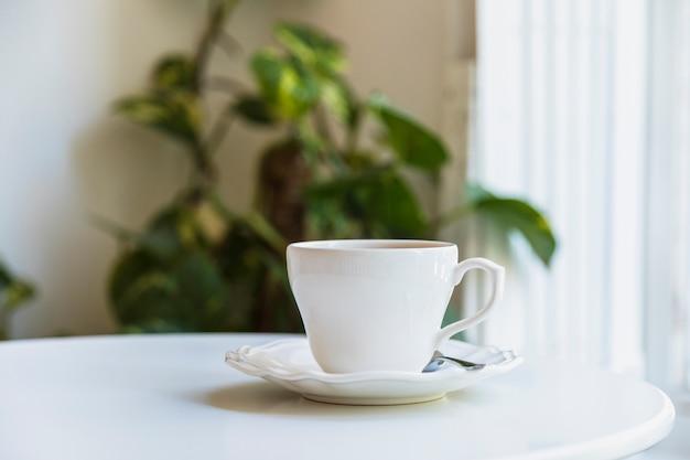 Xícara de café branca e colher em pires de cerâmica sobre a mesa branca
