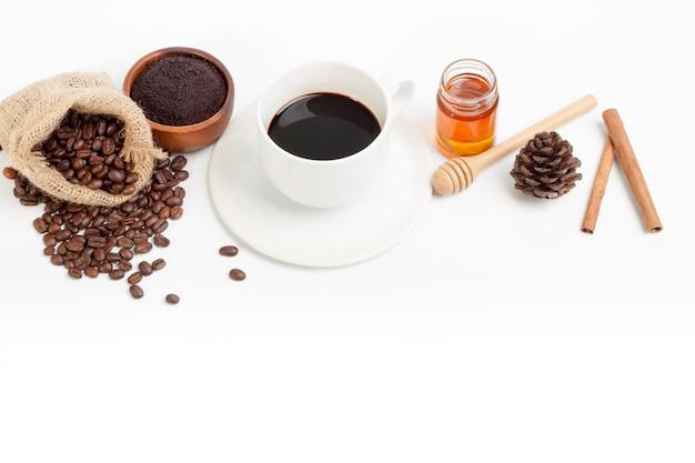 Xícara de café branca e grãos de café frescos mel açúcar na colher de pau branco