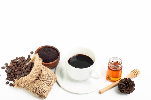 Xícara de café branca e grãos de café mel no fundo branco