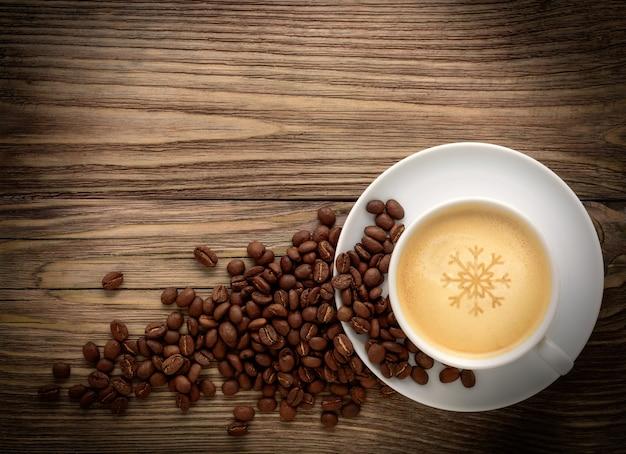 Xícara de café branca e grãos de café no antigo fundo escuro de madeira.