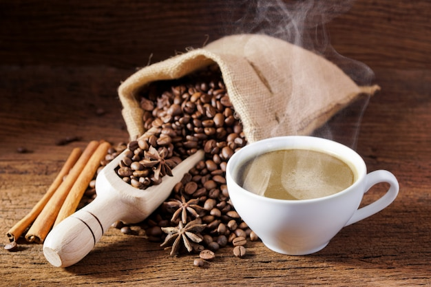 Xícara de café branca e grãos de café torrados em torno de