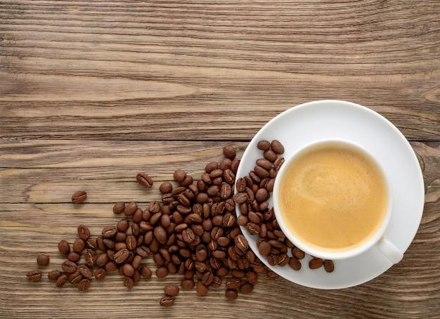 Xícara de café branca e grãos em fundo de madeira velho