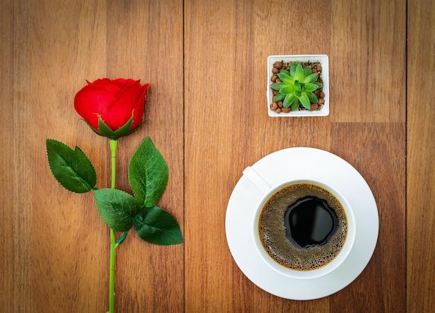 Xícara de café branca e rosa vermelha conceito dos namorados