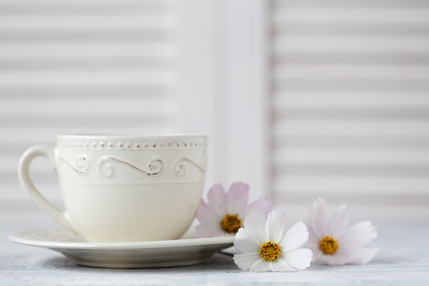 Xícara de café branca e um buquê de flores brancas close-up