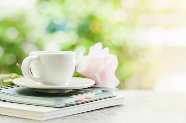 Xícara de café branca em cadernos espirais com flor rosa doce-de-rosa