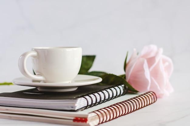 Xícara de café branca em cadernos espirais com rosa doce rosa contra o fundo de mármore branco