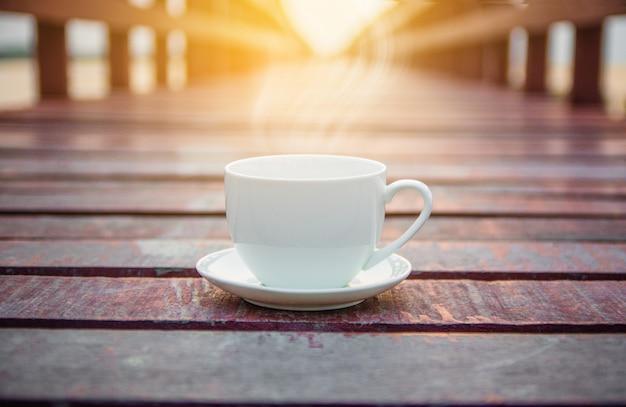 Xícara de café branca em fundo de madeira para o conceito de bebida de café
