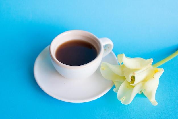 Xícara de café branca em um azul, flor. cafe da manha