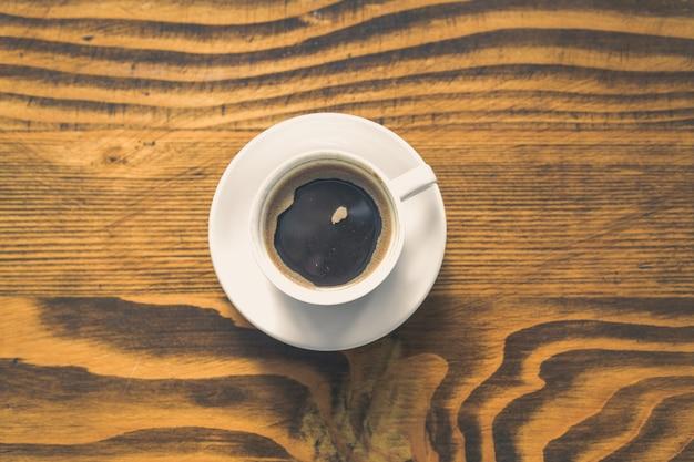 Xícara de café branca em uma mesa de madeira