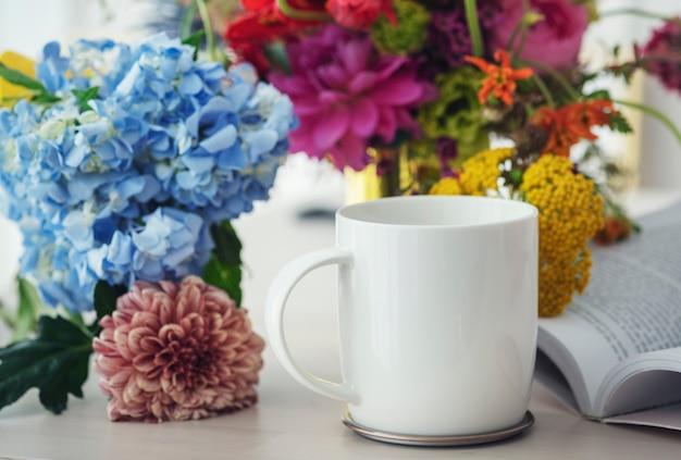 Xícara de café branca entre flores em uma mesa