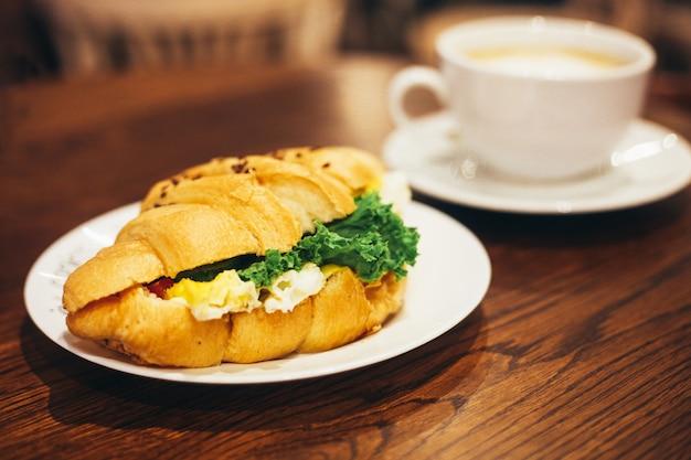 Xícara de café branca grande e croissant delicioso