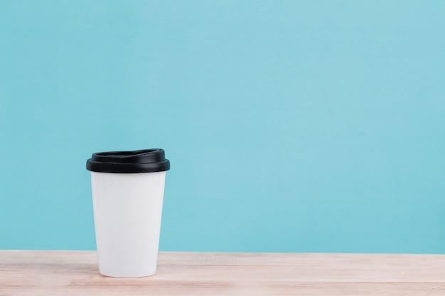 Xícara de café branca isolada na mesa de madeira