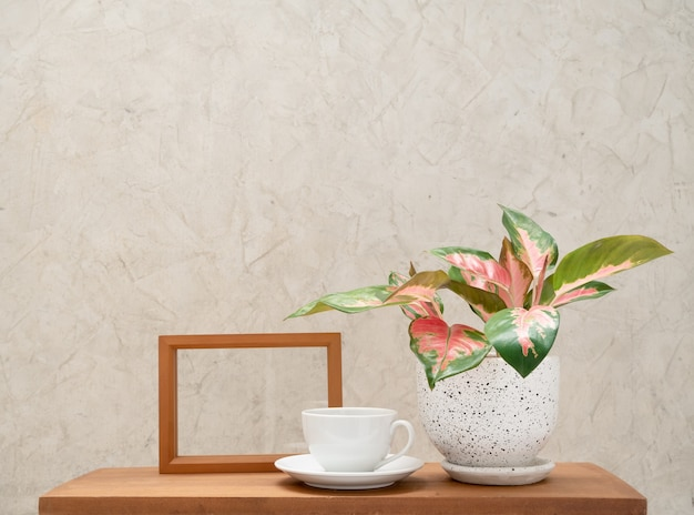 Xícara de café branca, moldura de madeira e planta de casa aglaonema (chinês evergreen) em uma decoração moderna de vaso de flores na mesa de madeira com fundo de parede de cimento