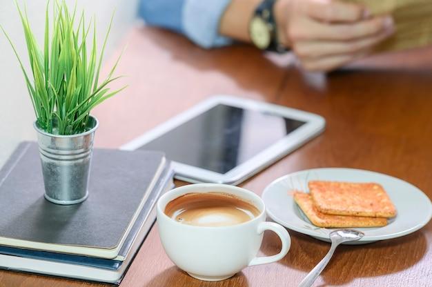 Xícara de café branca na mesa de madeira com imagem borrada do homem lendo o jornal de notícias.