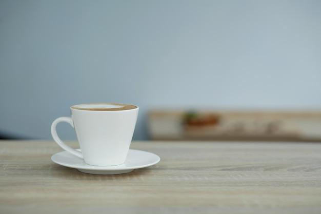 Xícara de café branca na mesa de madeira