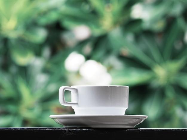 Xícara de café branca sobre floral verde.